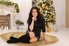 Sonrisas morenas hermosas de la muchacha y presentación mientras que se sienta en backg Imagen de archivo libre de regalías