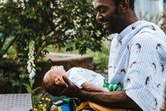 Sonrisas negras del padre de la alegría mientras que detiene a su bebé Imagen de archivo