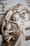 The sons console the weeping mother. The sons console the afflicted mother who weeps at the tomb stock photography
