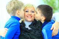 Sons Giving Mother Kiss Relaxing Royalty Free Stock Image