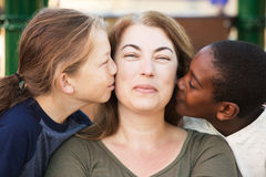 Sons kissing their mother. Happy mother being kissed on both sides of face by sons Stock Image