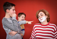 Sons and mother with shaving foam on her face. Smiling sons looking at their mother with shaving foam on her face Stock Photo