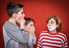 Sons and mother with shaving foam on her face. Surprised sons looking at their mother with shaving foam on her face Royalty Free Stock Images