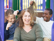 Sons playing with hair of mother. Laughing mother sitting with two sons playing with her hair Royalty Free Stock Photo