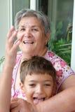 Sonson och hans farmor som har gyckel tillsammans Arkivfoto