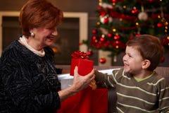 Sonson som ger julgåva Arkivbild