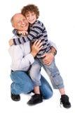 Sonson som kramar hans morfar, inomhus Royaltyfria Bilder