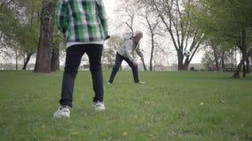 Sonson som sl?r bollen, och farfar som missa m?let Lycklig gullig pojke som hoppar i f?rgrundsstundgamala mannen stock video