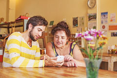 Sonson som undervisar hans farmor hur man använder mobiltelefonen Royaltyfri Bild