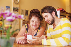 Sonson som undervisar hans farmor hur man använder mobiltelefonen Arkivfoton