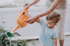 Sonsonen hjälper farmorvatten blommorna i trädgården royaltyfri foto