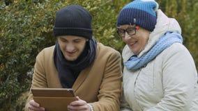 Sonsonen och mormodern talar med släktingar på den videopd appellen på minnestavlan utomhus lager videofilmer