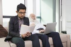 Sonsonläsebok medan farfar som hemma använder bärbara datorn på soffan Royaltyfria Foton