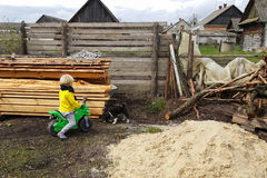 Sonsonpojken har gyckel på hans farmorhem i byn som spelar med en valp Royaltyfri Fotografi