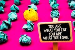 Sont l'écriture conceptuelle de main vous montrant ce que vous mangez Êtes vous ce que vous aimez Début des textes de photo d'aff Images stock