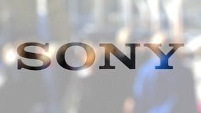 Sony Corporation logo on a glass against blurred crowd on the steet. Editorial 3D rendering. Sony Corporation logo on a glass against blurred crowd on the steet Stock Photography