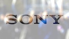 Sony Corporation logo on a glass against blurred crowd on the steet. Editorial 3D rendering. Sony Corporation logo on a glass against blurred crowd on the steet stock footage