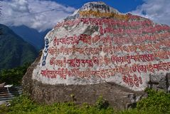 Buddhist prayer written over a rock royalty free stock photography