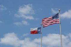 The American and The Texas Flag Blowing In The Wind. SONY DSC Here is The American and The Texas Flag Blowing In The Wind in a Blue Daytime Sky. The White clouds stock photography