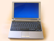 Sony laptop computer. Sony vaio VGN T350P laptop computer with blue screen, on a beige background royalty free stock photos