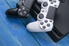 Sony PlayStation 4 ελεγκτής παιχνιδιών λεπτής 1Tb αναθεώρησης και 2 dualshock Κονσόλα παιχνιδιών με ένα πηδάλιο Κονσόλα παιχνιδιώ Στοκ Εικόνα