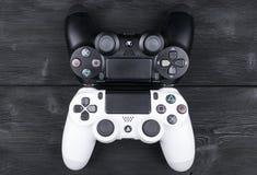 Sony PlayStation 4 ελεγκτής παιχνιδιών λεπτής 1Tb αναθεώρησης και 2 dualshock στο ξύλινο επιτραπέζιο υπόβαθρο Κονσόλα παιχνιδιών  Στοκ Φωτογραφίες
