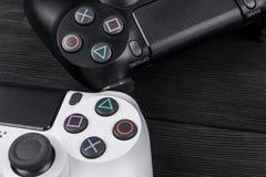 Sony PlayStation 4 ελεγκτής παιχνιδιών λεπτής 1Tb αναθεώρησης και 2 dualshock στο ξύλινο επιτραπέζιο υπόβαθρο Κονσόλα παιχνιδιών  Στοκ φωτογραφίες με δικαίωμα ελεύθερης χρήσης