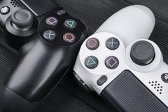 Sony PlayStation 4 ελεγκτής παιχνιδιών λεπτής 1Tb αναθεώρησης και 2 dualshock στο ξύλινο επιτραπέζιο υπόβαθρο Κονσόλα παιχνιδιών  Στοκ Φωτογραφία