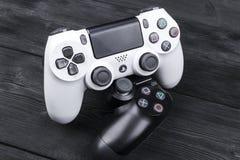 Sony PlayStation 4 ελεγκτής παιχνιδιών λεπτής 1Tb αναθεώρησης και 2 dualshock στο ξύλινο επιτραπέζιο υπόβαθρο Κονσόλα παιχνιδιών  Στοκ φωτογραφία με δικαίωμα ελεύθερης χρήσης