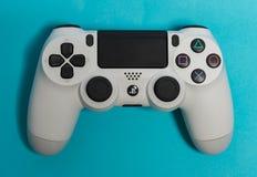 Sony PlayStation 4 ελεγκτής παιχνιδιών στον μπλε πυροβολισμό στούντιο υποβάθρου Στοκ Εικόνες