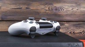 Sony PlayStation 4 λεπτός 1Tb ελεγκτής αναθεώρησης και dualshock παιχνιδιών στο ξύλινο υπόβαθρο Στοκ εικόνες με δικαίωμα ελεύθερης χρήσης