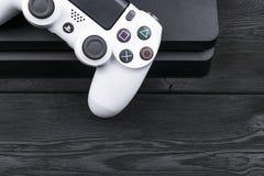 Sony PlayStation 4 λεπτός 1Tb ελεγκτής αναθεώρησης και dualshock παιχνιδιών στο ξύλινο επιτραπέζιο υπόβαθρο Κονσόλα παιχνιδιών οι Στοκ Εικόνες