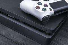 Sony PlayStation 4 λεπτός 1Tb και dualshock παιχνιδιών ελεγκτής Κονσόλα παιχνιδιών με ένα πηδάλιο Κονσόλα παιχνιδιών οικιακού βίν Στοκ Φωτογραφία