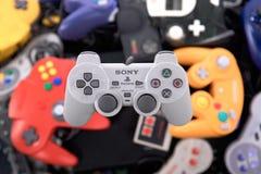 Sony Playstation Controller Hovering sobre una pila de reguladores retros del videojuego fotos de archivo libres de regalías