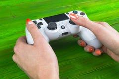 Sony PlayStation 4 het controlemechanisme van het dualshockspel in gamers overhandigt op wit achtergrondstudioschot Stock Afbeeldingen