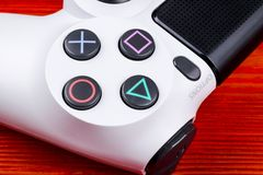 Sony PlayStation 4 Slim 1Tb revision and dualshock game controller. Game console with a joystick. Home video game console on red Royalty Free Stock Photo