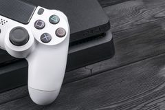 Sony PlayStation 4 Slim 1Tb revision and dualshock game controller. Game console with a joystick. Home video game console Royalty Free Stock Photos
