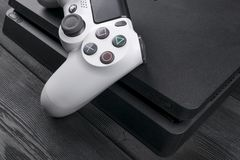 Sony PlayStation 4 Slim 1Tb revision and dualshock game controller. Game console with a joystick. Home video game console on wood. Sankt-Petersburg, Russia Stock Photo