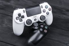 Sony PlayStation 4 Slim 1Tb revision and  2 dualshock game controller on the wooden table background. Home video game console Royalty Free Stock Photography