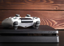 Sony PlayStation 4 Slim 1Tb revision and game controller on the wood surface. Sankt-Petersburg, Russia - 14 August, 2017: Sony PlayStation 4 Slim 1Tb revision Stock Image