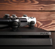 Sony PlayStation 4 Slim 1Tb revision and game controllers on the wood surface. Sankt-Petersburg, Russia - 14 August, 2017: Sony PlayStation 4 Slim 1Tb revision stock photography