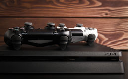 Sony PlayStation 4 Slim 1Tb revision and game controllers on the wood surface. Sankt-Petersburg, Russia - 14 August, 2017: Sony PlayStation 4 Slim 1Tb revision royalty free stock photo