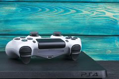 Sony PlayStation 4 Szczupłego 1Tb i dualshock gemowego kontrolera na błękitnym drewnianym tle Obraz Royalty Free