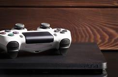 Sony PlayStation 4 1Tb przeglądu i gry Szczupły kontroler na drewnie ukazuje się Fotografia Royalty Free