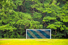 Soocer goal in Forest. Soccer goal with blue and white net in front of a green forest stock photo