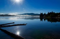 Sooke Harbor Reflection. The morning sun rises over Sooke Harbour burning off the fog casting its reflection in the calm waters Stock Images