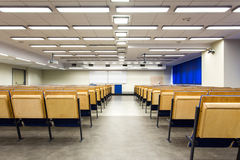 Soon, all the seats will be taken. Shot from behind of a lecture hall towards whiteboard Stock Photos