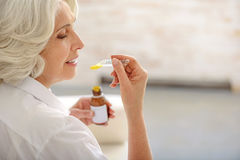 Soon I will be healthy. Positively motivated old woman is curing herself by cough syrup. She is sitting and smiling royalty free stock images