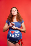 Soon I will be mother. Portrait of pregnant woman in blue tanktop and polka-dot panties holding alarm-clock and looking upwards on red background Stock Photos