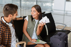 Soon my dream will come true. Excited young women is showing flight tickets to her boyfriend with aspiration. They are sitting at airport and smiling royalty free stock photo